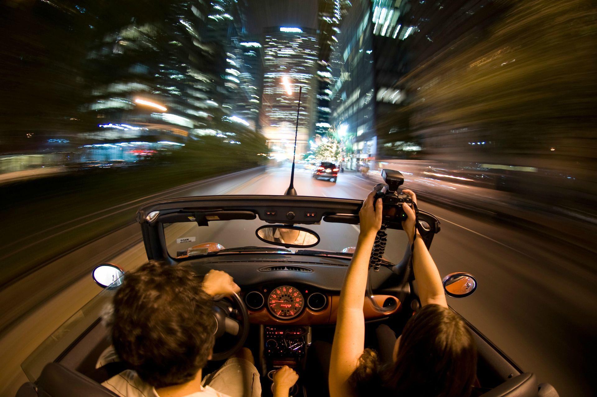 driving car night town city fast shutter speed blur