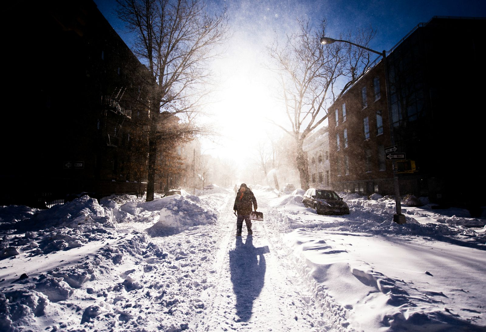 man shoveling snow after blizzard
